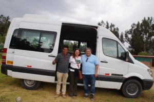 A group of people smiling before entering a van to begin their trip