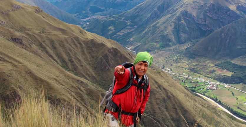 someone pointing and smiling at the camera as they stand on a trail high above a valley