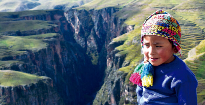 Child Dressed in a Peruvian hat smiling in front of the Ananiso Canyon