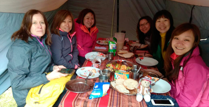 Group of smiling women eating in a tent near the Humantay Lagoon