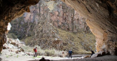 A group of trekkers stand near the entrance of a cave within a canyon in the Peruvian Andes