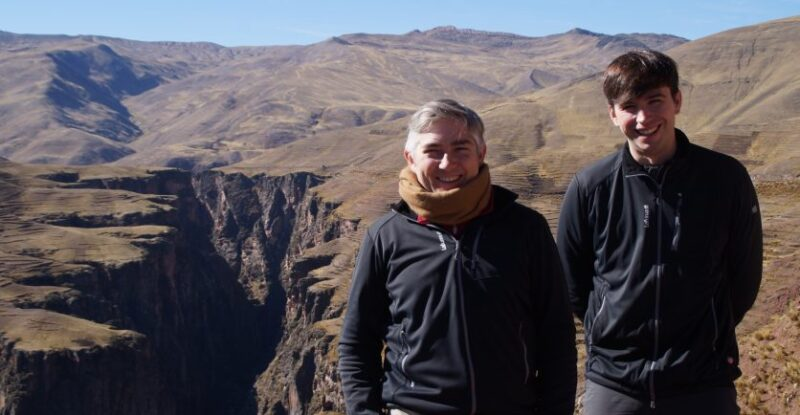 Two men smiling for the camera as they stand near the top of a canyon in the Peruvian Andes