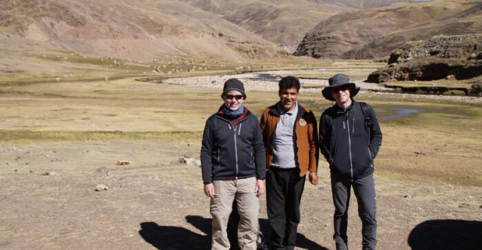 a group of smiling men trekking in the Peruvian Andes with Alpaca grazing in the distance