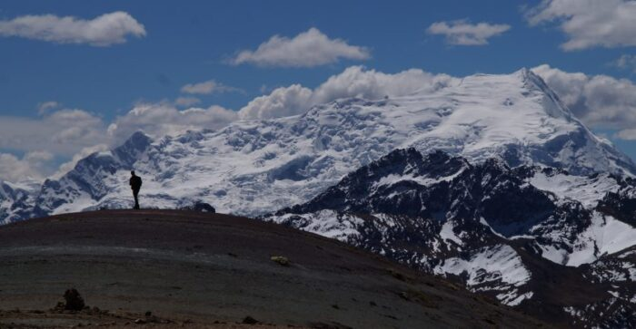 A lone trekker taking in the views of the snow-capped mountains in the Peruvian Andes
