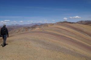 A trekker walking along the top of one of the Rainbow Coloured Mountains on a clear sunny day