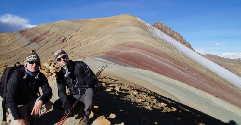 Two Trekkers smiling for a photo on a ridge near the top of one of the Rainbow Coloured Mountains near Cusco