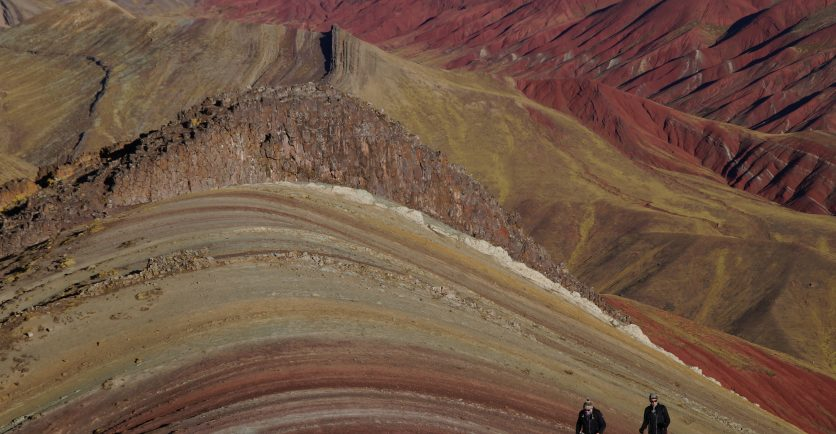 Two people trekking to the top of one of the Rainbow Mountains near Cusco