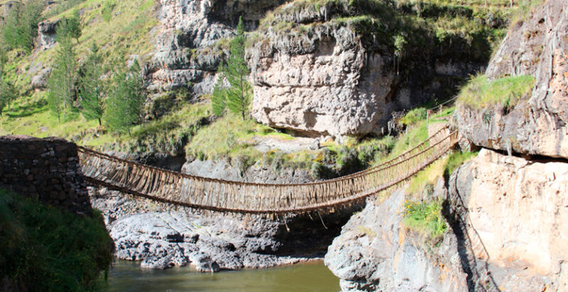 side view of the inca bridge crossing with grassy mountain sides in the distance
