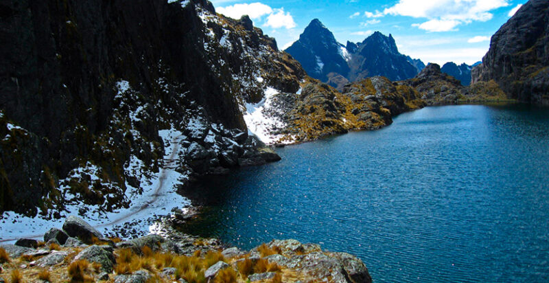 Overlooking a lake in the Lares valley which is surrounded by snow kissed cliffs